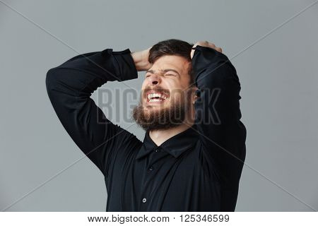 Frustrated businessman standing over gray background