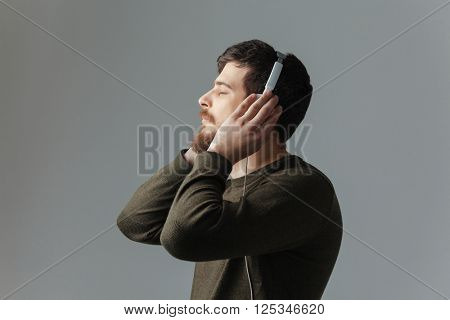 Side view portrait of a young man listening music in headphones over gray background