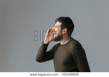 Side view portrait of a man shouting over gray background