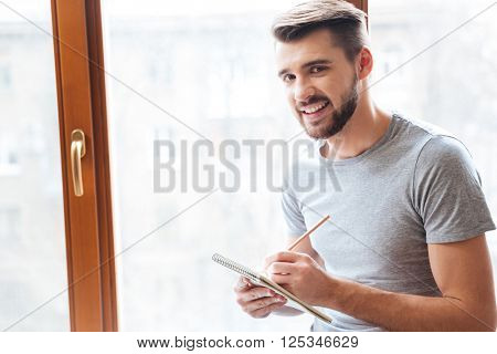 Cheerful attractive young man writing in notepad near the window at home
