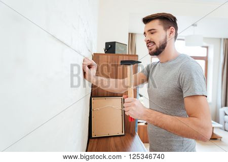 Handsome bearded young man hammering nail on the wall at home