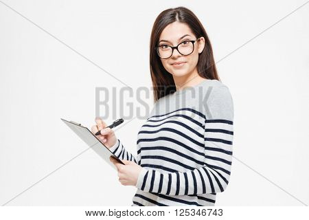 Happy woman writing notes in clipboard and looking at camera isolated on a white background