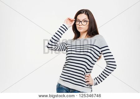 Serious casual woman in glasses looking at camera isolated on a white background