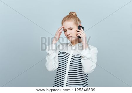 Pensive woman talking on the phone isolated on a white background