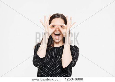 Cheerful woman looking at camera through fingers isolated on a white background