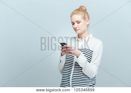 Young woman using smartphone isolated on a white background