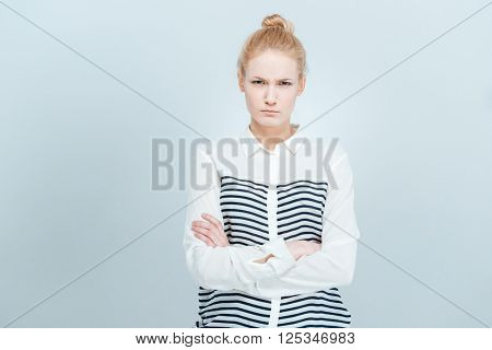 Angry woman with arms folded standing isolated on a white bakground