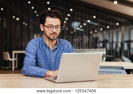 Casual man working with laptop computer in office