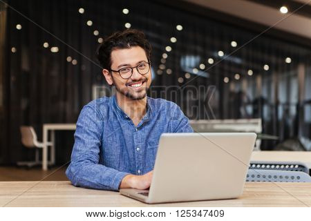 Happy man using laptop computer in office