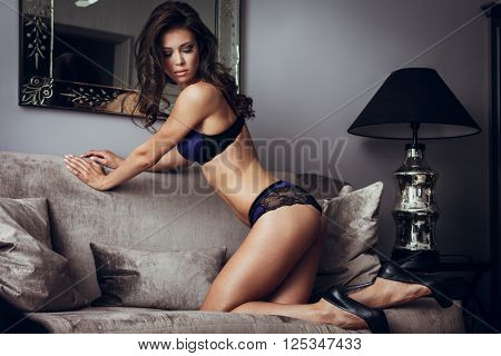 Beautiful lady in sexy lingerie sits on a sofa