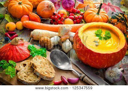 Pumpkin soup in an open pumpkin on a wooden table