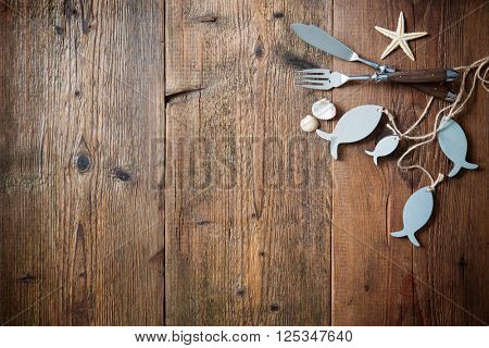 Fish cutlery tied with empty fish shaped tag on wooden table with copy space. Menu card for restaurants