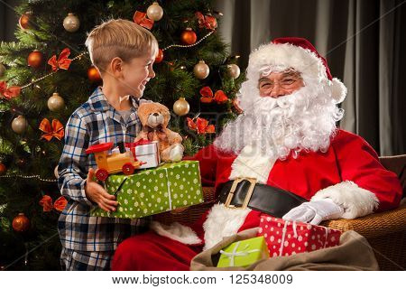 Santa Claus and a little boy. Boy holding gifts in front of Christmas Tree