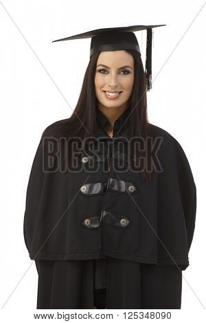 Portrait of happy young female graduate in academic dress smiling.