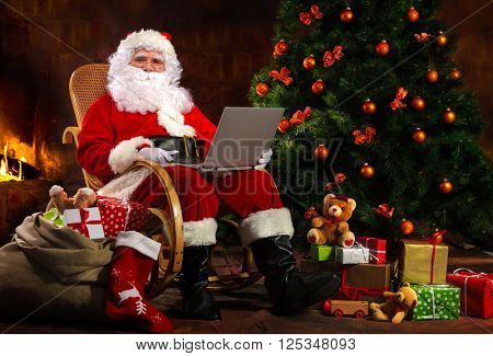 Santa Claus sitting in front of fireplace near Christmas tree with a laptop
