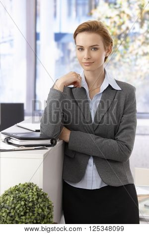 Portrait of pretty young businesswoman standing, looking at camera.