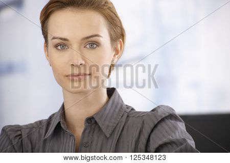 Closeup portrait of beautiful young businesswoman looking at camera.
