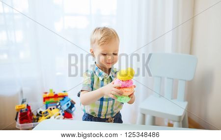 childhood, creativity, arts, activity and people concept - happy little baby boy playing with ball clay at home