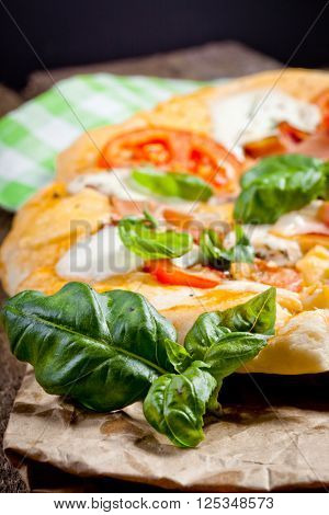 Pizza with prosciutto, mozzarella, tomatoes and basil, selective focus