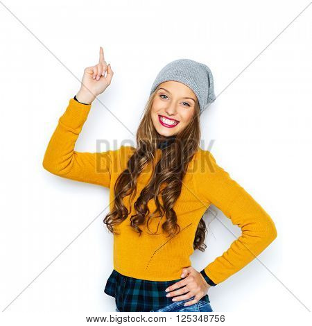 people, style and fashion concept - happy young woman or teen girl in casual clothes and hipster hat pointing finger up