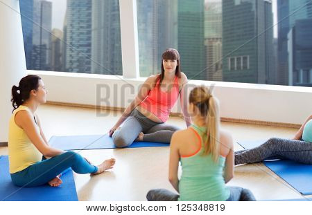 pregnancy, sport, fitness, people and healthy lifestyle concept - group of happy pregnant women sitting and talking on mats in gym