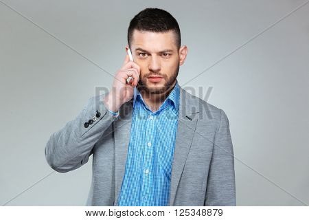 Angry businessman talking on the phone and looking at camera over gray background