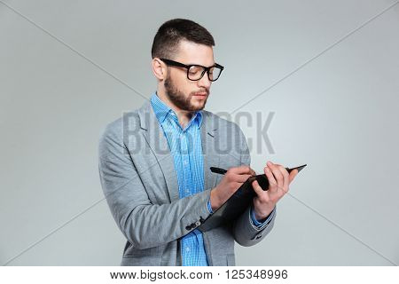 Businessman writing notes in clipboard over gray background