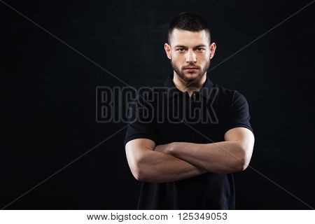 Handsome man with arms folded standing over black background and looking at camera