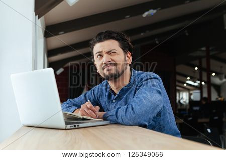 Pensive casual man working in office