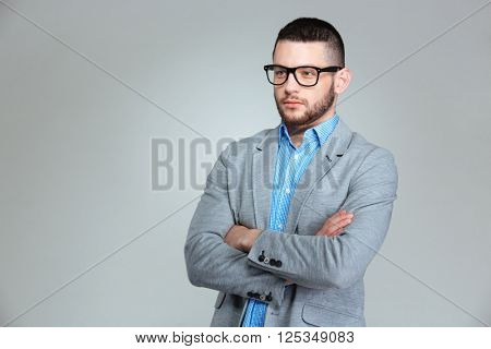 Pensive businessman standing with arms folded over gray background