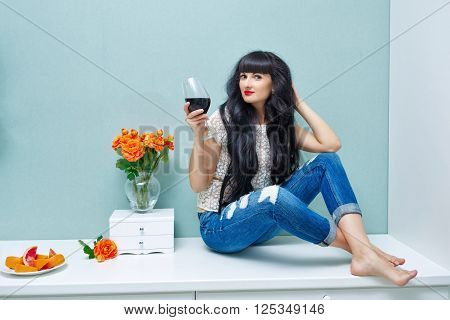 Young attractive woman drinking red wine at home. Relax after work. Girl barefoot and with her long hair.