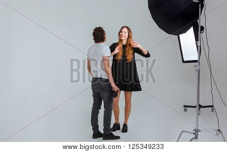 Male photographer speaking with female model in studio with equipments