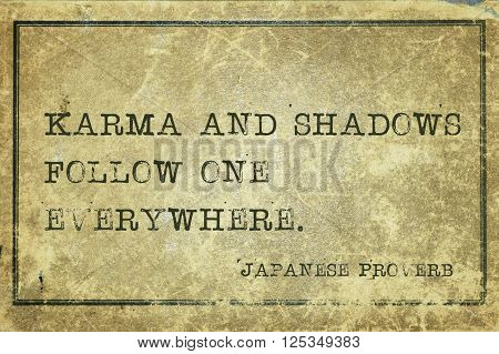 Karma and shadows follow one everywhere - ancient Japanese proverb printed on grunge vintage cardboard