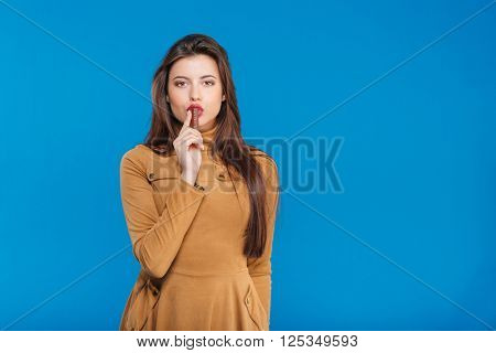 Seductive pretty young woman standing and eating chocolate candy bar over blue background