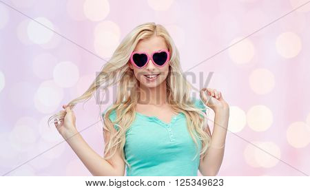 emotions, expressions, summer and people concept - smiling young woman or teenage girl in heart shape sunglasses holding her strand of hair over pink holidays lights background