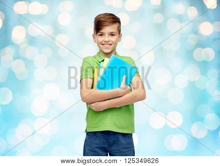 childhood, school, education and people concept - happy smiling student boy with folders and notebooks over blue holidays lights background