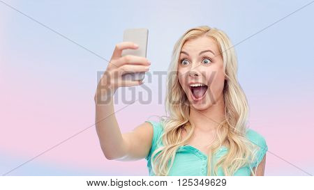 emotions, expressions and people concept - happy smiling young woman or teenage girl taking selfie with smartphone over pink background