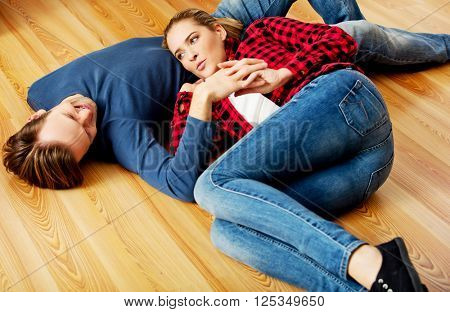Young happy couple lying on the floor