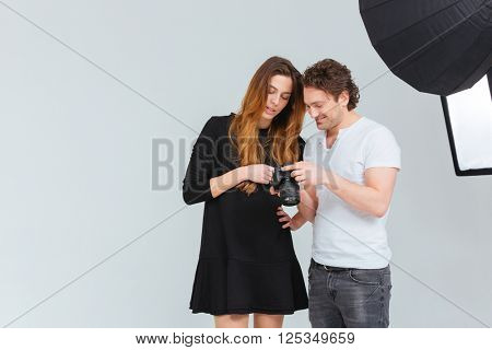 Male photographer with female model looking on camera screen