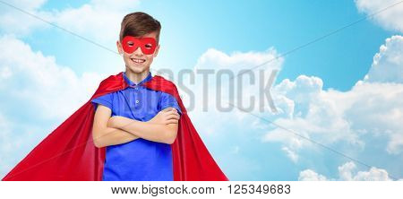 carnival, childhood, power, gesture and people concept - happy boy in red super hero cape and mask over blue sky and clouds background
