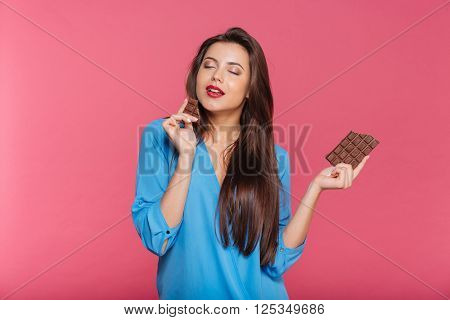 Sensual attractive young woman eating chocolate over pink background