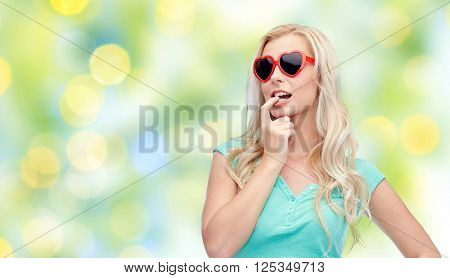 emotions, expressions, summer and people concept - smiling young woman or teenage girl in sunglasses over summer green lights background