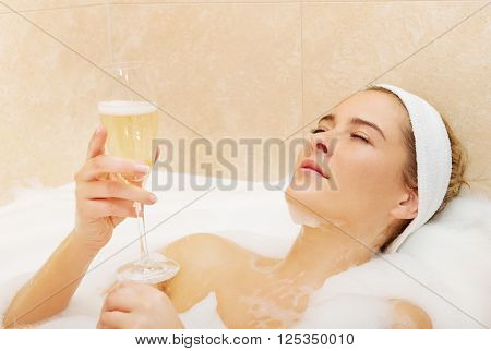 Woman relaxing in bath with glass of champagne