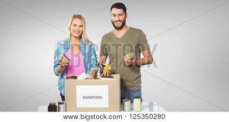 Portrait of happy colleagues smiling while holding products against grey vignette