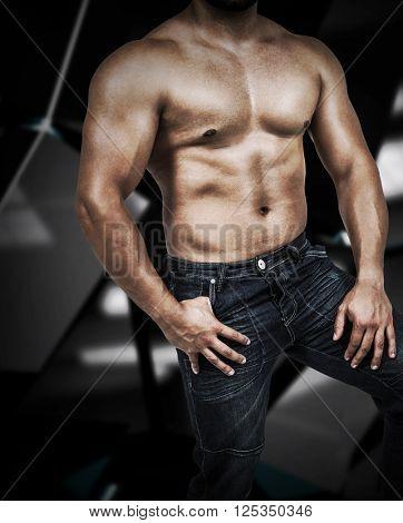 Muscular man wearing blue jeans against black angular design