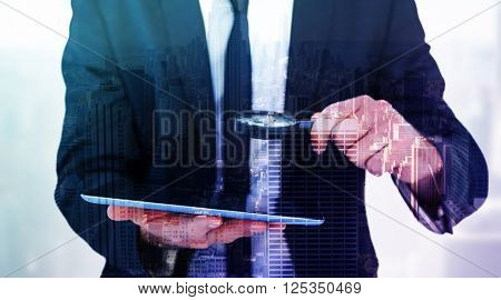 Businessman looking at his tablet through magnifying glass against city skyline