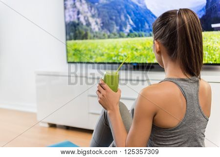 Home woman drinking green smoothie watching tv show on television with weight loss vegetarian diet healthy juice during online fitness dvd workout videos in living room.
