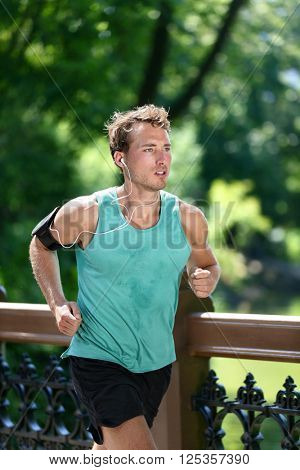 Runner running listening to music with earbuds and fitness armband with workout app. Male athlete training during summer in urban New York city Central park sweating in sportswear activewear clothing.