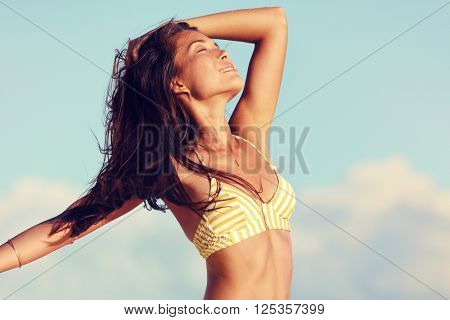 Bikini freedom woman feeling free in sexy weight loss body relaxing in sunset. Asian girl in swimwear relaxing on beach vacation with open arms in hair living a healthy lifestyle.