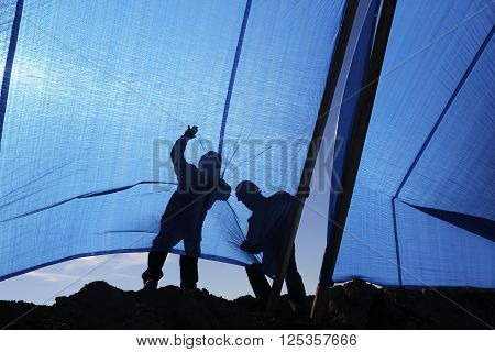 Workers pull a fabric screens to protect from the sun